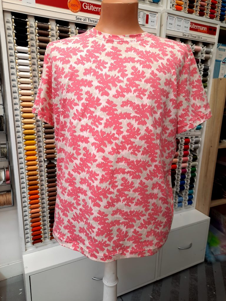 pink camo print t-shirt on mannequin in front of a thread display